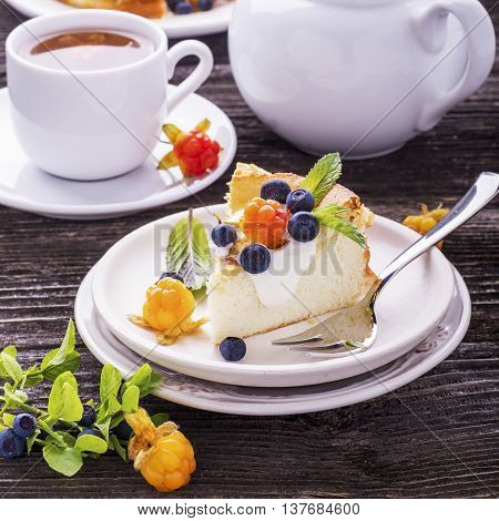 Homemade breakfast. Fresh cheesecake with Nordic berries cloudberries and blueberries in plain wooden background served with cloudberry tea in a white ceramic bowl. Decorated branches forest blueberries