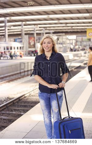 Woman with suitcase waiting for the train
