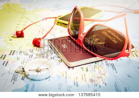 Travel concept Red sunglasses passport compass smart phone and earphones on europe map