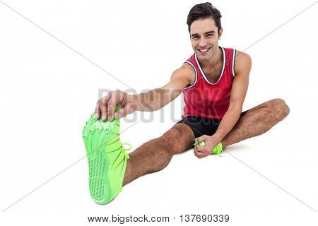 Portrait of male athlete doing stretching exercise on white background
