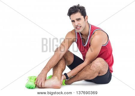 Portrait of male athlete with foot pain on isolated white background