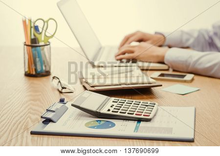 Man Analysis Business on wood desk. Close up of accountant or banker making calculations.
