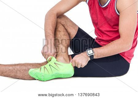 Male athlete wearing his sport shoes and getting ready for sport on white background