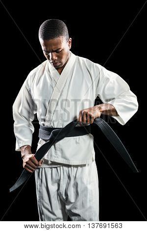 Portrait of fighter tightening karate belt on black background