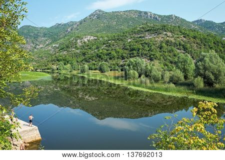 Skadar Park view with fisherman on the river Rijeka Crnojevica, Montenegro