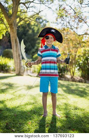 Portrait of smiling boy pretending to be a pirate in the park on a sunny day