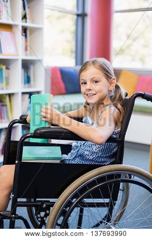 Portrait of disabled school girl on wheelchair holding a books in library at school