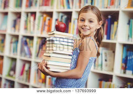 Portrait of school girl holding stack of books with apple in library at school