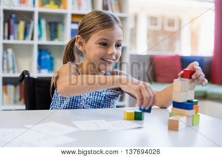 Smiling school girl playing with building block in library at school