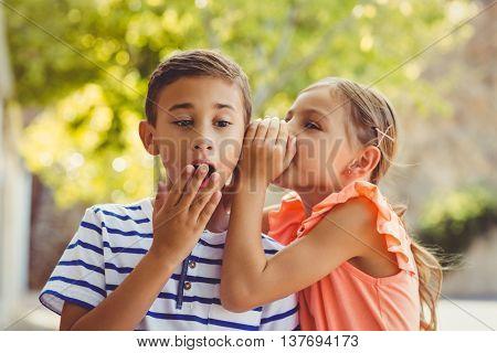 Girl whispering a secret in boys ear in school