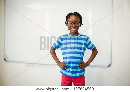 Portrait of happy schoolboy smiling in classroom with hand on hip at school