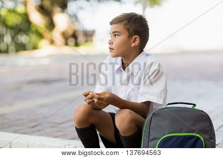 Thoughtful schoolboy sitting alone in campus at school