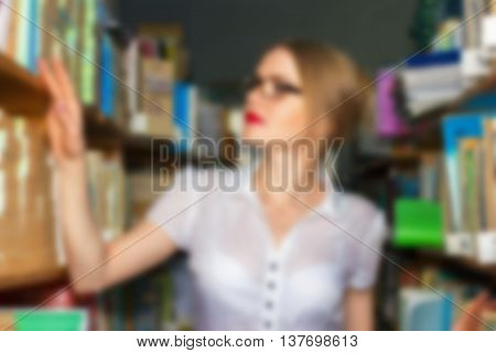 Girl In The Library Between Racks With Books Looking Beautiful Blonde With Glasses Gets Knowledge An