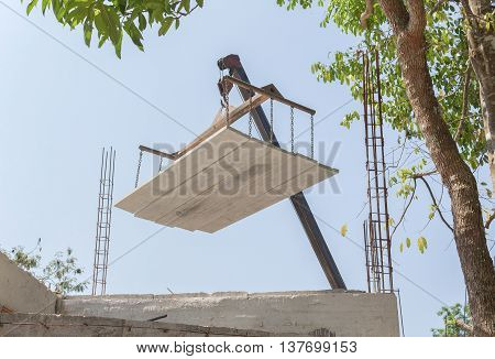 Industrial Crane operating works loading of cement sheet In construction.