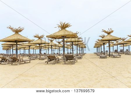 Beach with thatched umbrellas and wooden loungers.