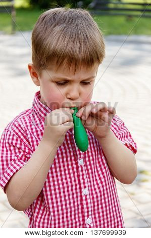 Boy Inflates The Rubber Balloon, Playing In The Park On A Background Of Green Trees, Smiling, Soft F
