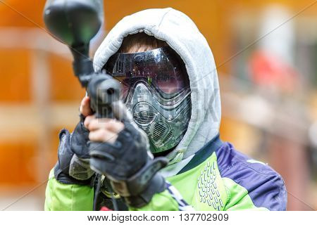 Cool paintball player aiming in camera. Closeup.