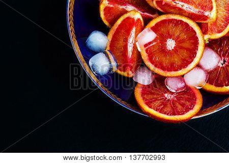 Sliced Sicilian red oranges on dark-blue plate. Black stone background top view.