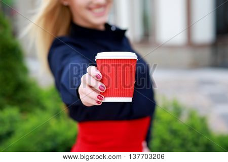 female hands holding paper cup closeup. Happy and smiling woman showing cup with coffee sunny day.coffee break