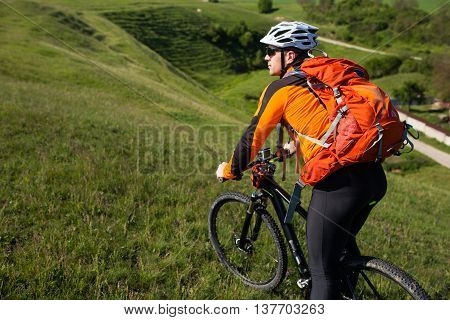 Cyclist in orange jersey on the Beautiful Meadow Trail