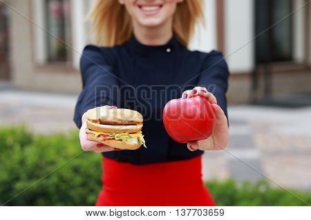 Burger and apple closeup. Women's hands holding healthy and unhealthy food. Food choice concept.
