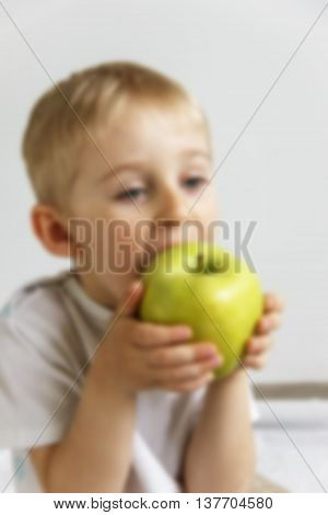 Happy Cheerful Boy Eats The Big Apple, The Child Is The Fruit Green, Blurred