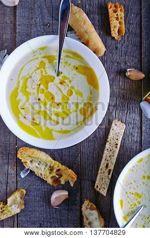Homemade garlic cream soup with toasted ciabatta on dark and old wood background
