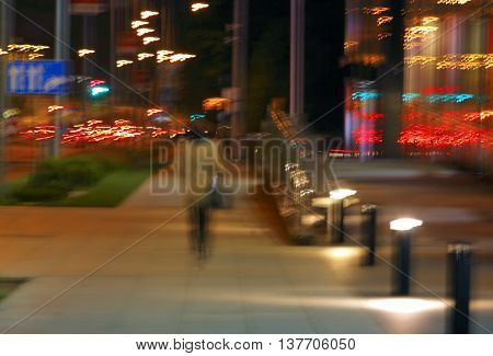 Abstract blurred background of woman walking in city at night