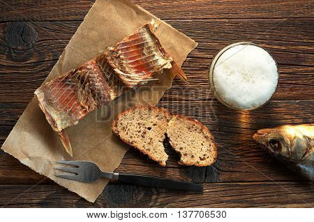 Salted fish on a paper and glass of beer on old wooden table top view