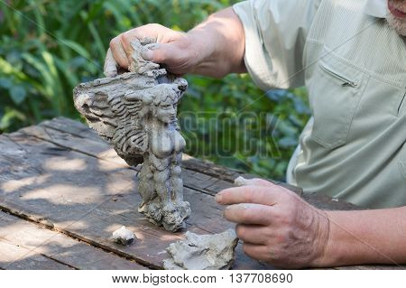 sculptor making sculpture outdoor, working with clay