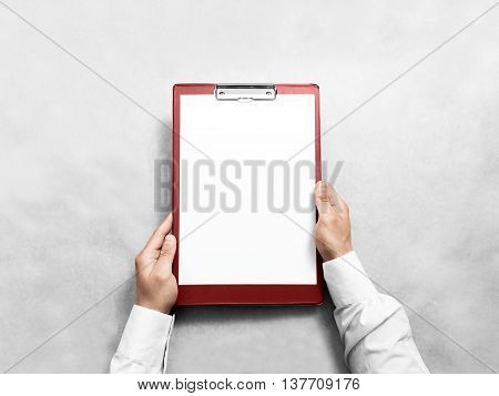 Hand holding blank red clipboard with white paper design mockup. Clear a4 document folder mock up template hold in arm. Clipboard notepad surface display front. Checklist tablet file presentation.