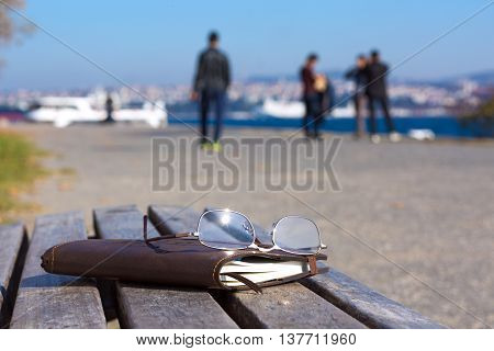 Creative composition with leather Notepad and Glasses on wood bench seafront blurred People walking on background