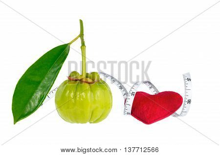 Garcinia cambogia fresh fruit with red heart and measuring tape isolated on white. Garcinia is spice plants. It helps in the metabolism contain high vitamin C and hydroxy citric acids for weight loss