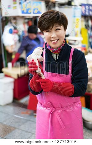 Busan South Korea - March 13 2016: Asian woman selling a small shark in the fish market in Jagalchi in Busan South Korea