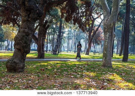 An attractive Young woman wearing a colorful head covering and Muslim Dress Walking in University Park