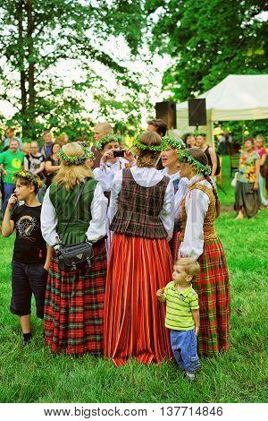 Vilnius Lithuania - June 23 2016: Midsummer Festival in Verkiai Park in Vilnius Lithuania. The festival is called Rasos Festival. Women wearing national dress and flower wreaths.
