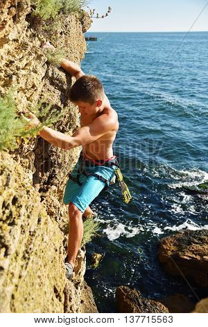 Male Climber Climbs On Rocky Wall