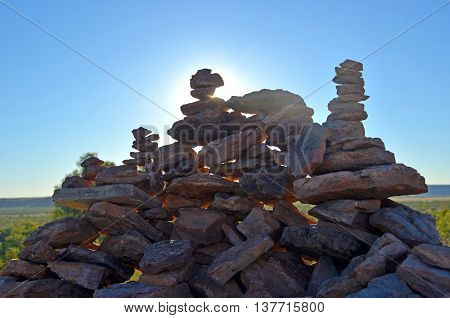 Sun shining behind rock cairns in outback Queensland, Australia