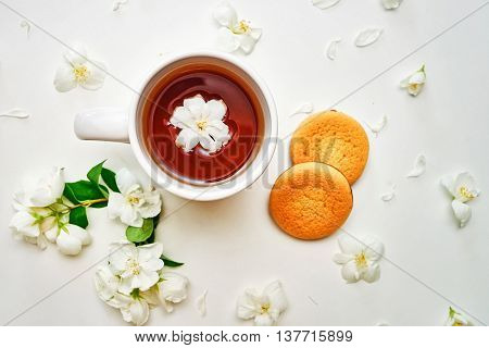 Tea Cup With Jasmine Flowers And Biscuits In White Background