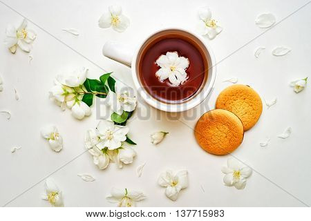 Tea Cup With Fragrant Jasmine Flowers And Biscuits In Background