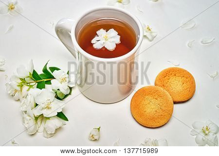 Tea Cup With Fragrant Jasmine Flowers And Cookies In Background