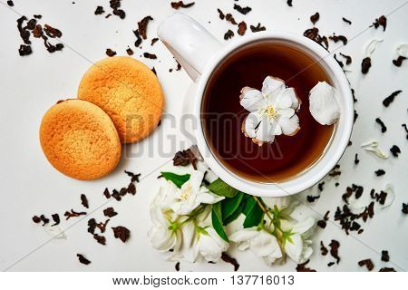 Teacup With Dried And Fresh Jasmine Flowers And Cookies