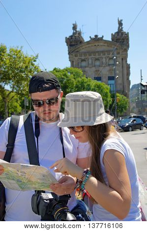 Tourists Looking At A City Map In La Rambla Street