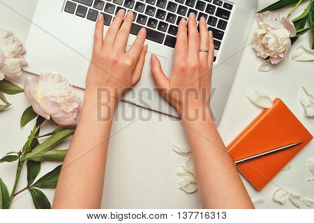 Workspace with laptop female hands notebook pen and peony flowers on the white background. Flat lay top view. Freelancer working place