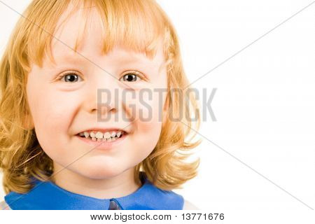 Portrait of little redhead girl happily smiling and looking at camera