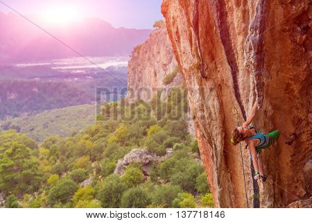 Young cute Female Climber Hanging on one hand on rocky Wall over colorful forest with backlight shining Sun