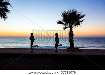 Two People Man and Woman jogging on Seafront making Morning Fitness Tropical Palm Tree colorful Dawn blue Sea. Focus on Palm Tree and paved path, joggers body slightly blurred in motion