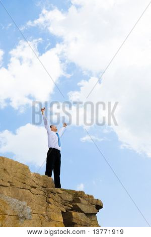 Photo of joyful businessman looking at bright sky with his arms raised expressing happiness and enjoyment