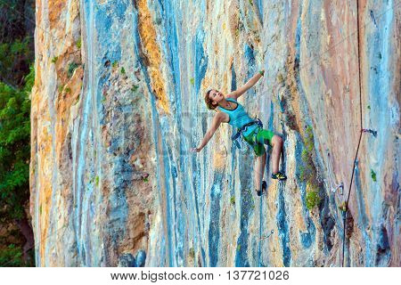 Young Female Climber ascending vertical rocky wall sporty Clothing Blue Shirt Green Pants using Rope and other Safety Gear