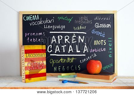 Blackboard in a classroom with the message LEARN CATALAN and some text